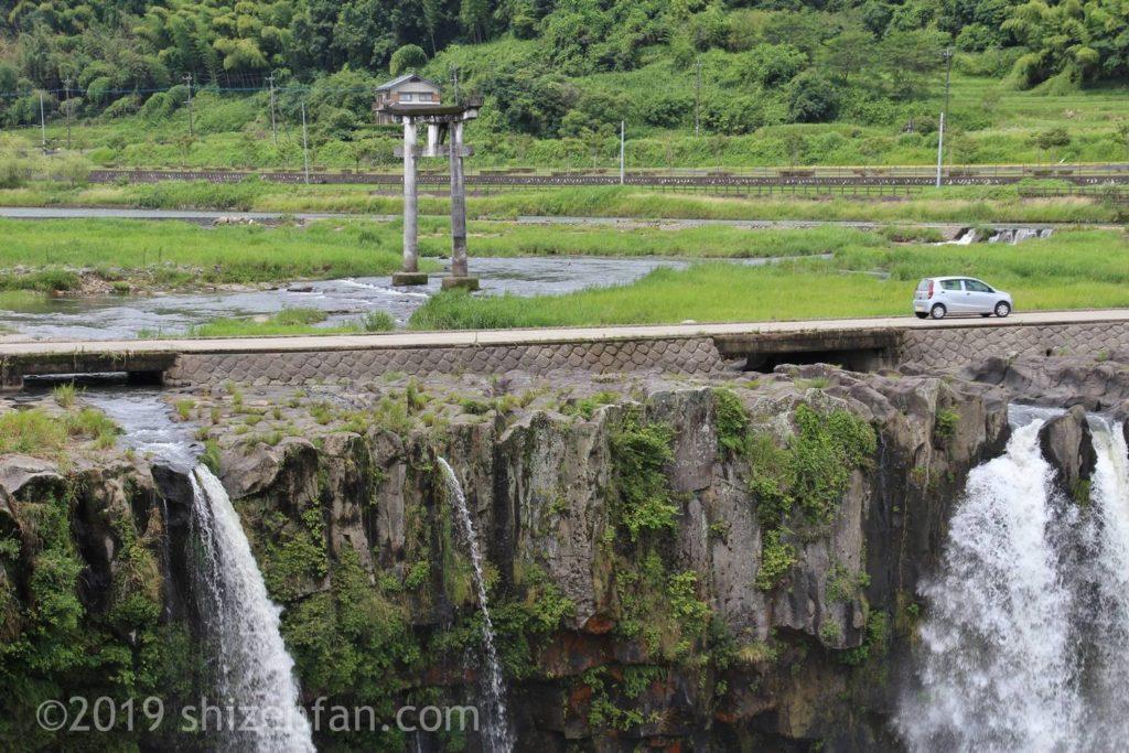 原尻の滝の上の道路とその上を走る車
