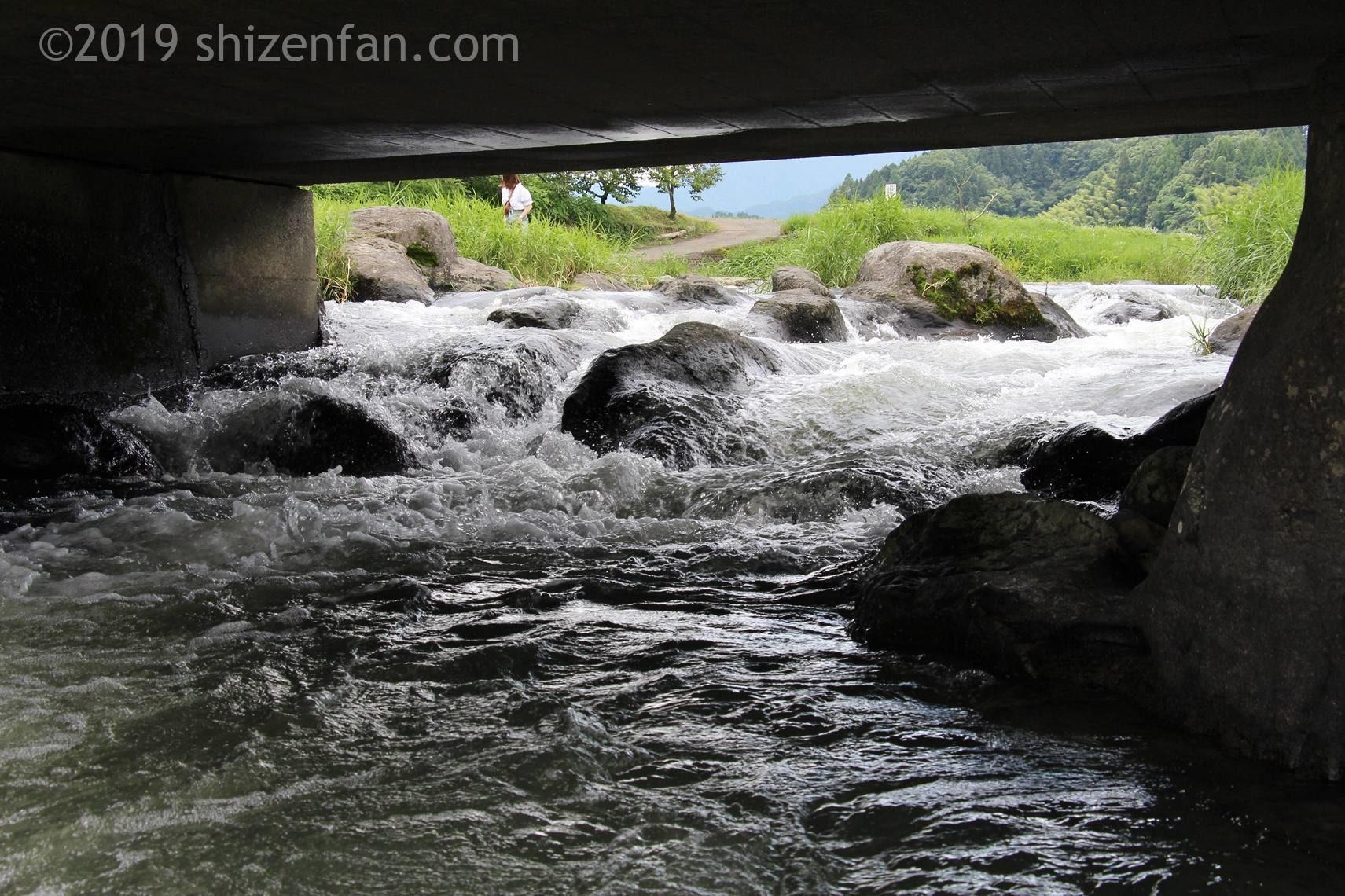 原尻の滝の上にある道路下を通る激しい水の流れ