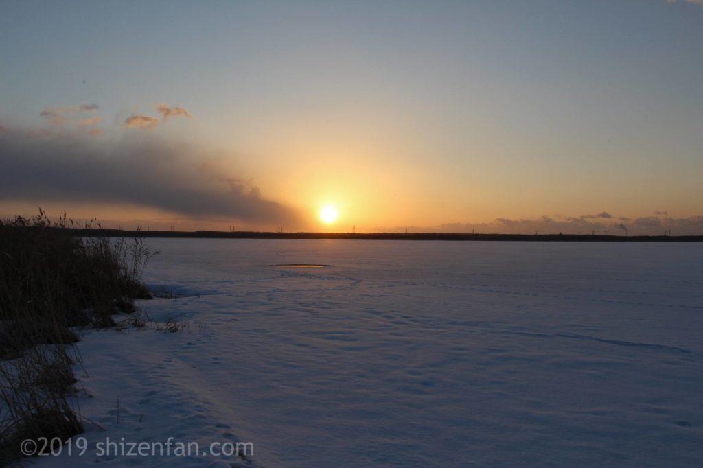 冬のウトナイ湖の白く凍った湖面とオレンジ色の朝日