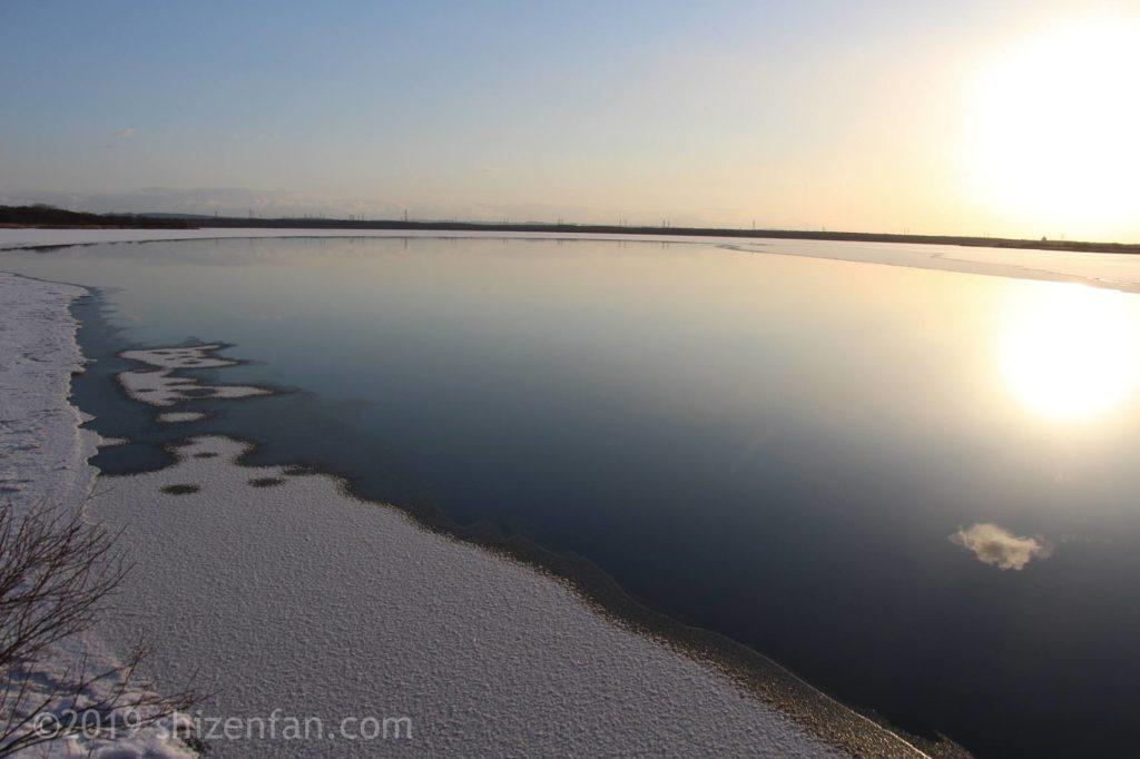 冬のウトナイ湖の朝、湖面に映る朝日と白く凍る水際