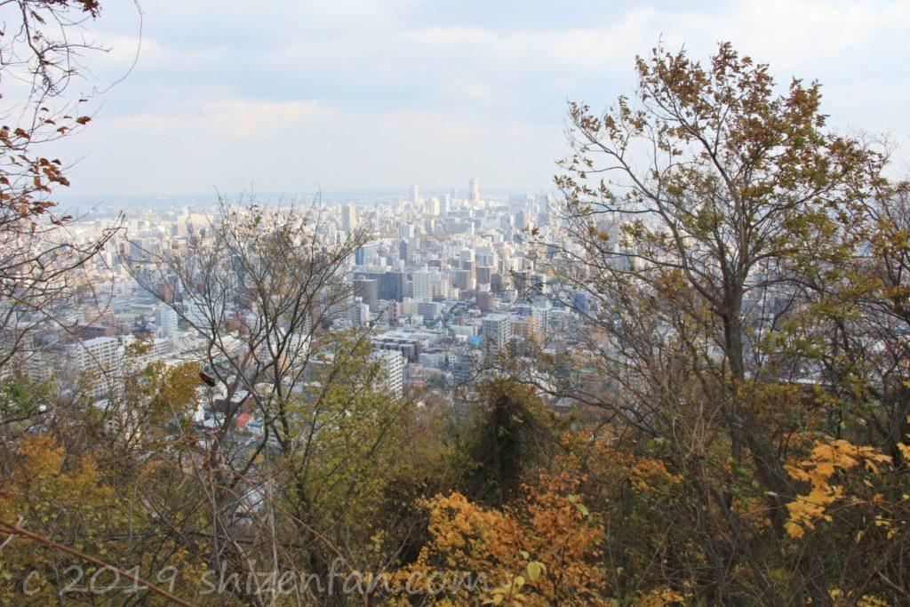 秋の札幌円山原始林、登山道の木々の隙間から見える札幌の街