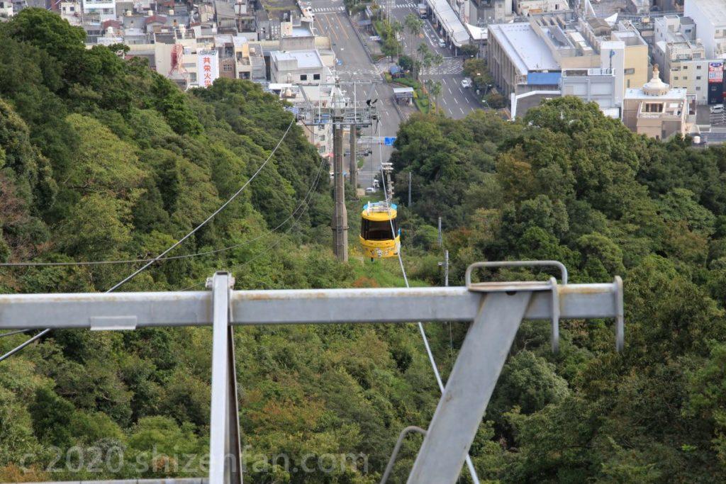 黄色の眉山ロープウェイが山を上がってくる様子