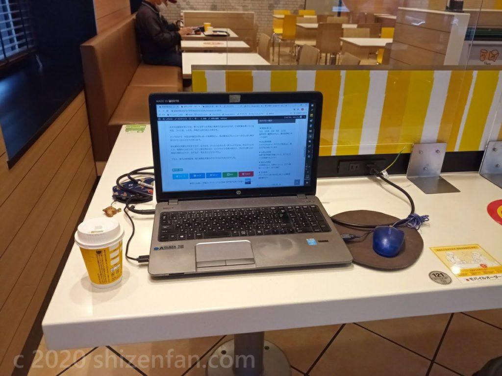 マクドナルドの充電席で開かれたノートパソコンとコーヒーの紙カップ