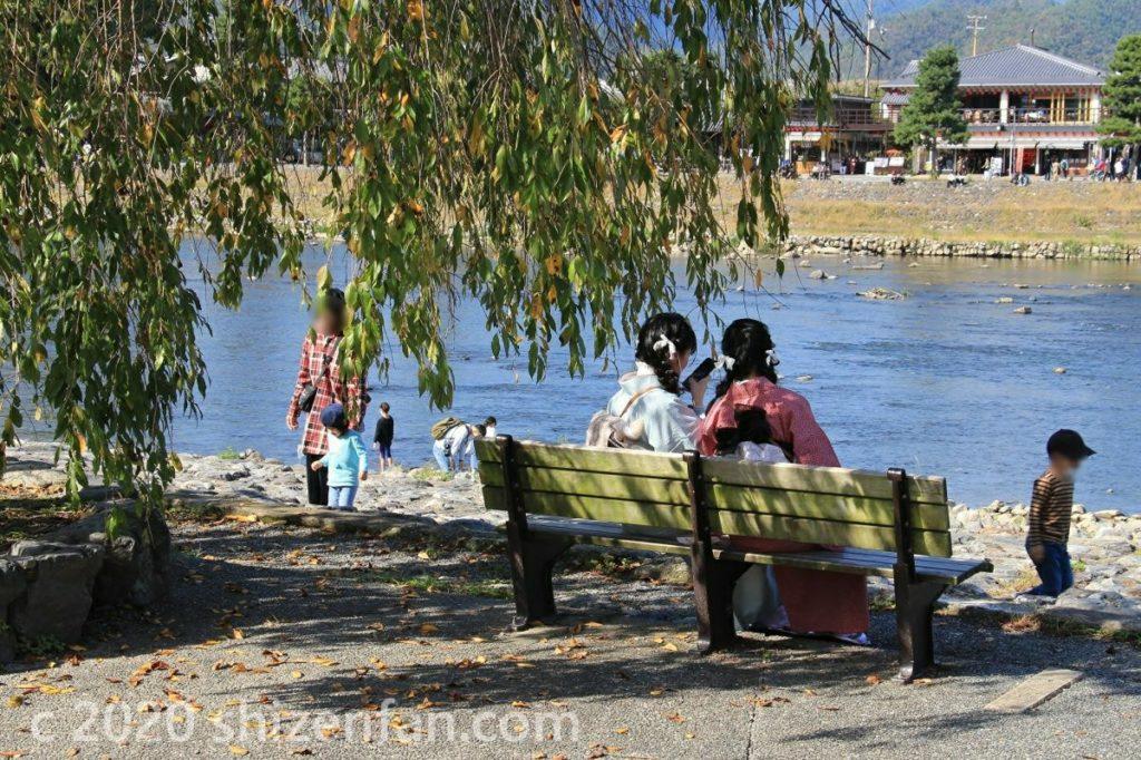 京都・嵐山の川辺の風景(ベンチに座る2人の和装女子)