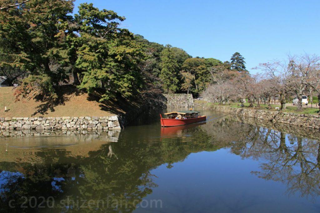 晴天の彦根城のお堀を進む一艘の屋形船