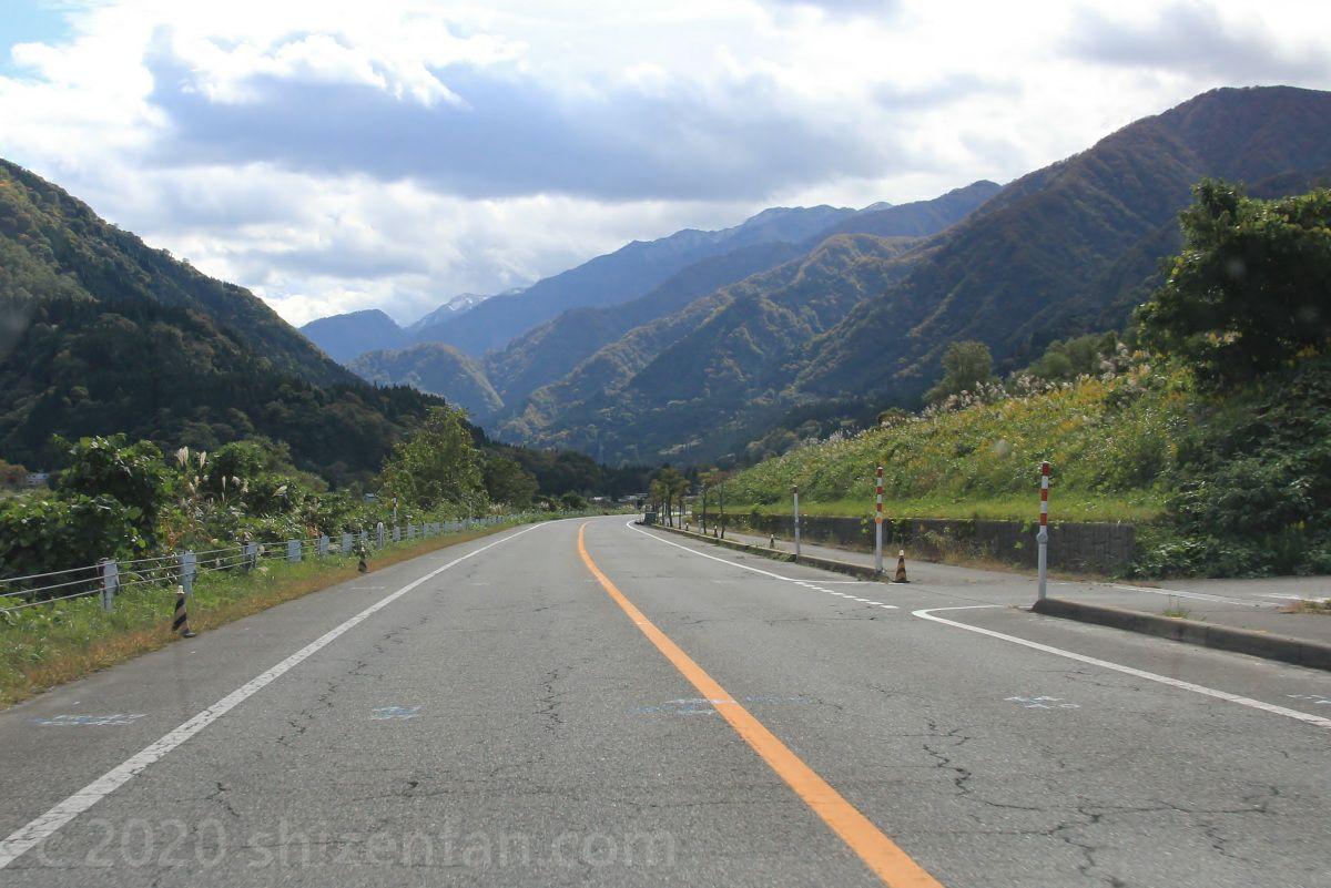 中央がオレンジラインの車道 奥に北アルプスの山々