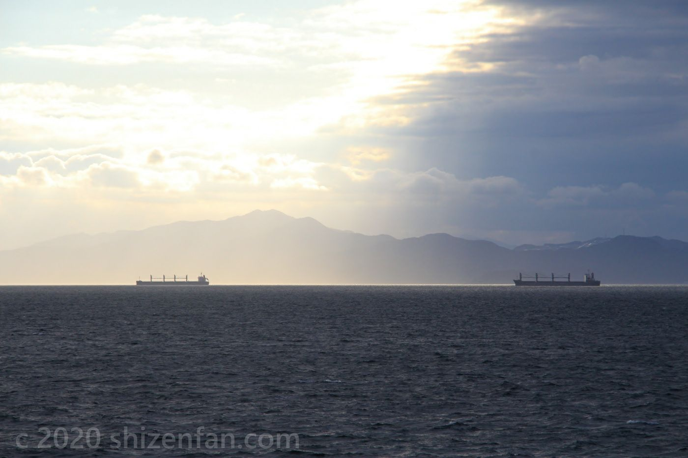 明暗の分かれた空模様と海上に浮かぶ二艘の船