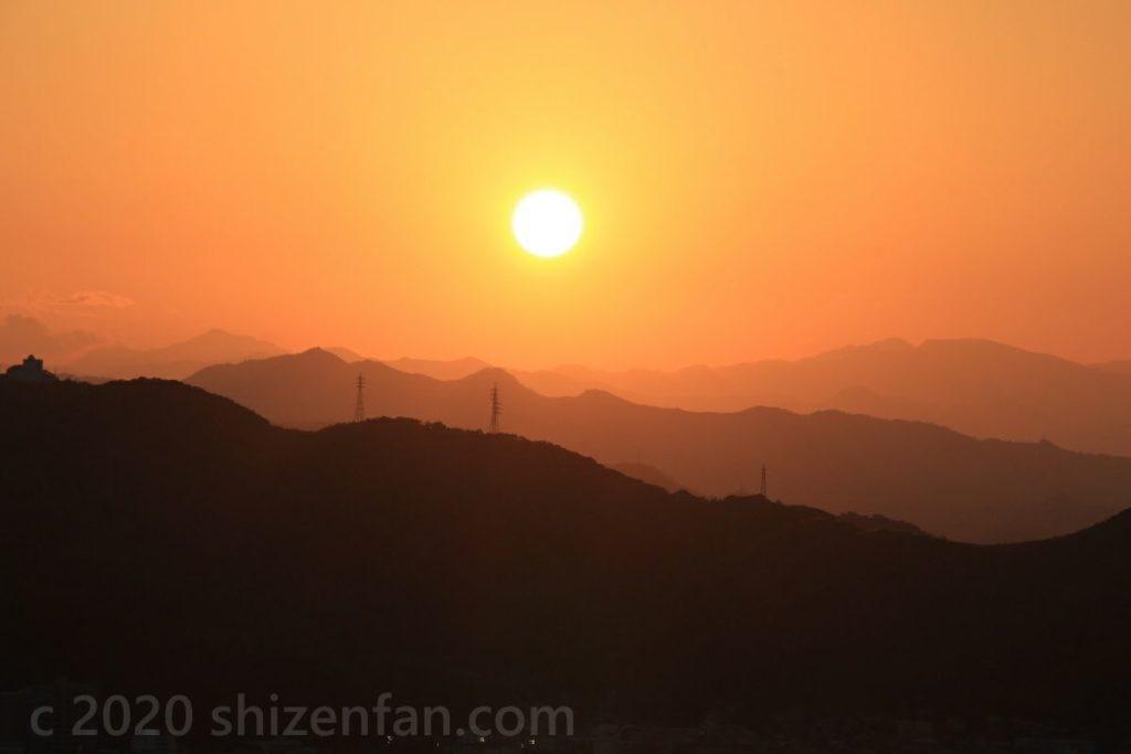 幾重にも重なる山影と雲一つないオレンジ色の空、ぽっかり浮かんだ夕日