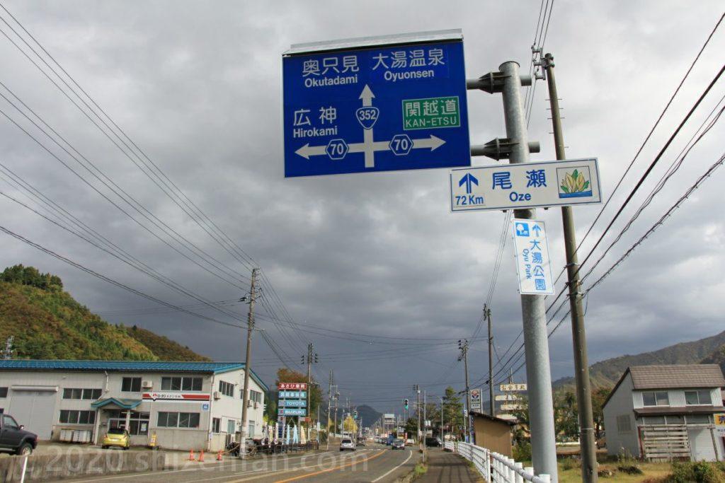魚沼(小出)から奥只見方面を示す青看板と「尾瀬72km」の道路標示