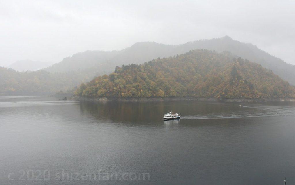霧に包まれた雨の奥只見湖と、湖上を往く一隻の遊覧船