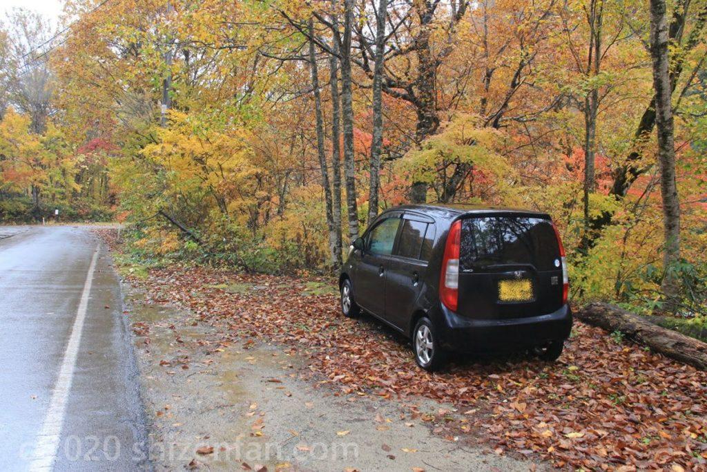 紅葉した木々に囲まれた道路の路側帯に停車した黒い軽自動車