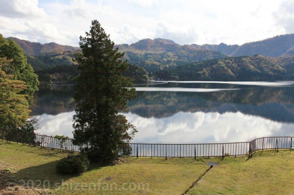 山と空を湖面に映した沼沢湖と一本の木