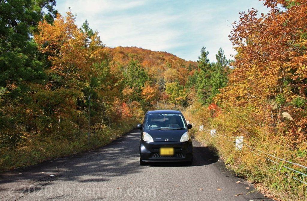 紅葉期の福島西部の峠道を越える黒い軽自動車