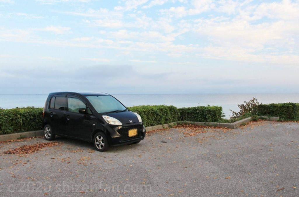 湖沿いの駐車場に停まる1台の黒い軽自動車(ホンダライフ)